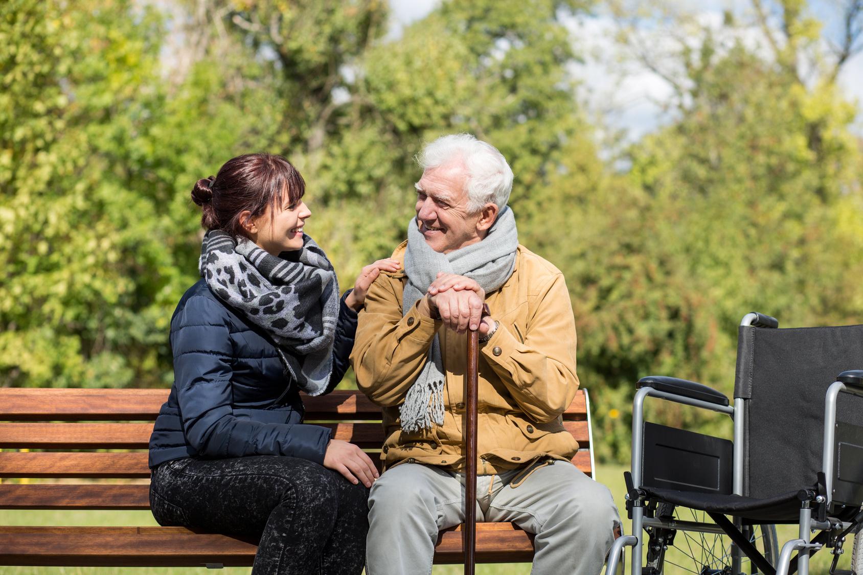 Elder man and carer in the park